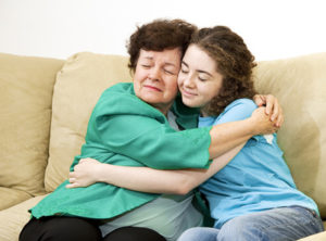 Mother and teenage daughter giving each other a big hug.